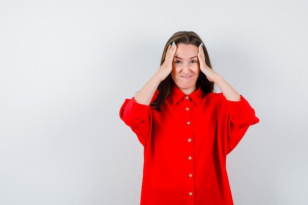 Mulher jovem, mantendo as mãos na cabeça na blusa vermelha e parecendo esquecida. vista frontal.
