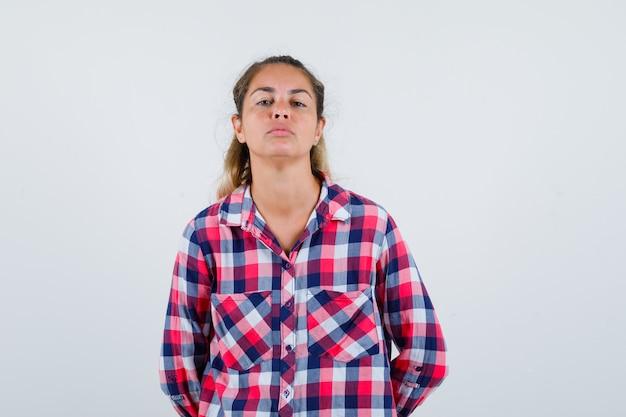 Mulher jovem, mantendo as mãos para trás em uma camisa casual e parecendo triste. vista frontal.