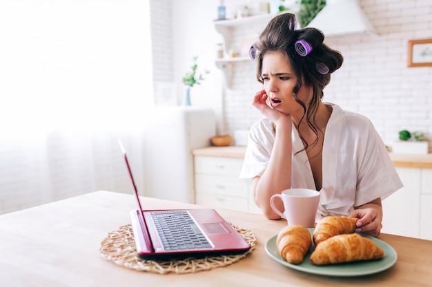 Mulher jovem maravilhada espantada olhar no laptop. assistindo filme na cozinha. croissant e copo de bebida na mesa. governanta descuidada no quarto. vida com o nosso trabalho. luz do dia de manhã.