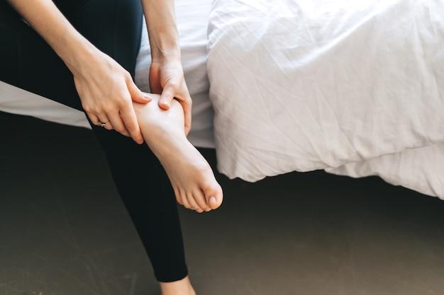 Mulher jovem massageando o pé na cama branca após o treino ou um árduo dia de trabalho.