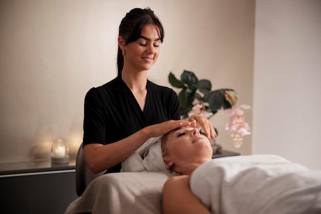 Mulher jovem massageando o rosto do cliente