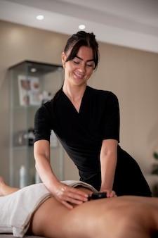 Mulher jovem massageando seu cliente em seu salão de beleza