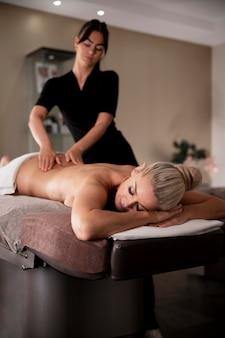 Mulher jovem massageando seu cliente