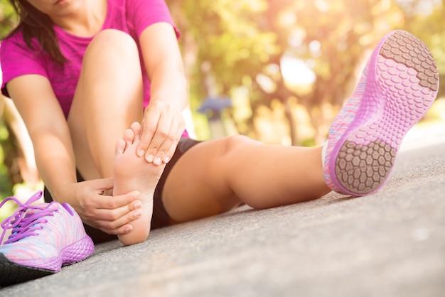 Mulher jovem, massaging, dela, doloroso, pé, de, exercitar, e, executando