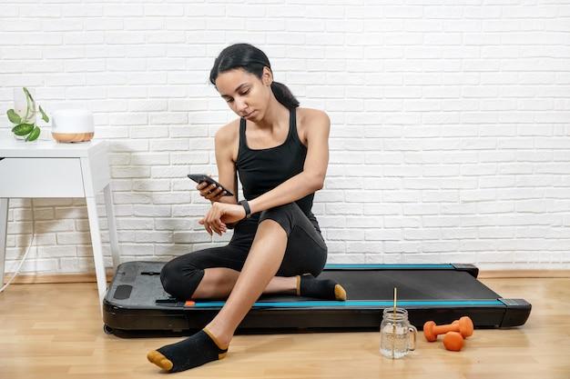 Mulher jovem mede o controle de atividade com smartphone e pulseira de fitness após o treino em casa. treinamento avançado em casa com dispositivos digitais. conceito de novas tecnologias