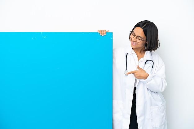 Mulher jovem médica de raça mista com um grande cartaz isolado no fundo branco apontando com o dedo indicador uma ótima ideia