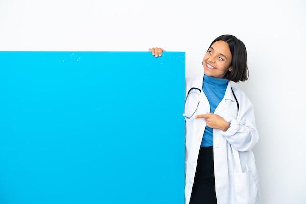 Mulher jovem médica de raça mista com um grande cartaz isolado no fundo branco apontando uma ótima ideia