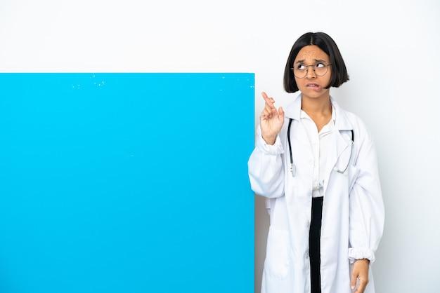 Mulher jovem médica de raça mista com um grande cartaz isolado no fundo branco com os dedos se cruzando e desejando o melhor