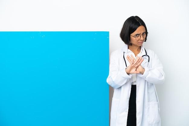 Mulher jovem médica de raça mista com um grande cartaz isolado no fundo branco fazendo gesto de pare com a mão para parar um ato