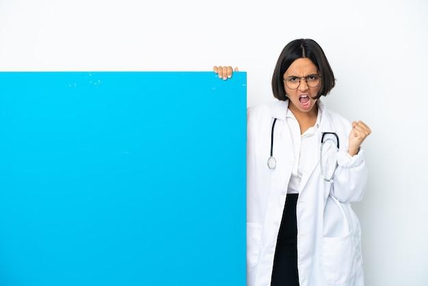 Mulher jovem médica de raça mista com um grande cartaz isolado no fundo branco frustrada por uma situação ruim