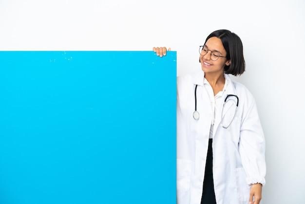 Mulher jovem médica de raça mista com um grande cartaz isolado no fundo branco olhando para cima enquanto sorri