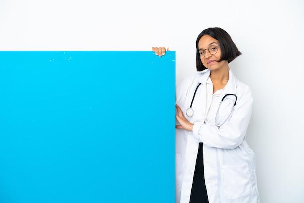 Mulher jovem médica de raça mista com um grande cartaz isolado no fundo branco rindo