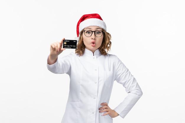 Mulher jovem médica segurando um cartão de banco na mesa branca.