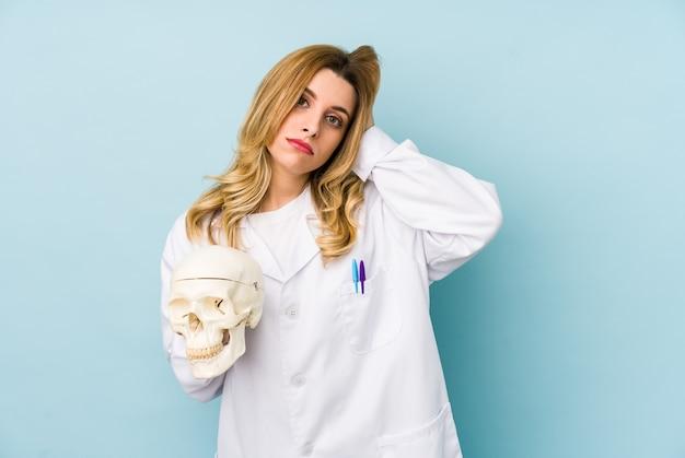 Mulher jovem médica segurando um crânio isolado em choque, ela se lembrou de um encontro importante.
