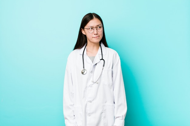 Mulher jovem médico chinês confuso, sente-se duvidoso e inseguro.