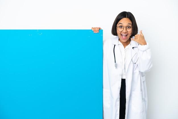 Mulher jovem médico de raça mista com um grande cartaz isolado no fundo branco, fazendo gesto de telefone. ligue-me de volta sinal