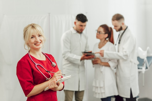 Mulher jovem médico de uniforme vermelho com um notebook no escritório. mulher olhando para a câmera.