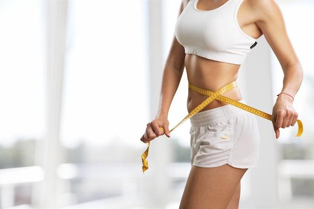 Mulher jovem medindo a cintura no fundo
