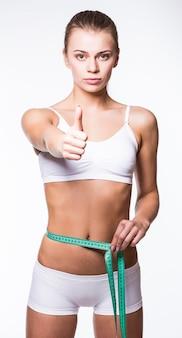 Mulher jovem medindo a forma perfeita do conceito de estilos de vida saudáveis de coxas bonitas