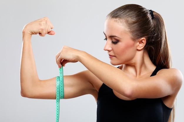 Mulher jovem, medindo braço