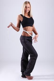 Mulher jovem, medindo cintura, com, fita métrica