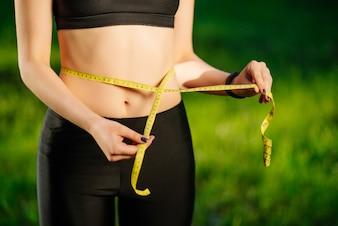 Mulher jovem, medindo, dela, cintura fina, com, um, fita métrica