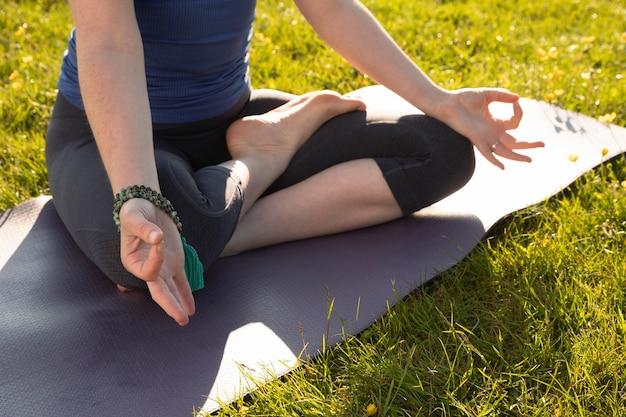 Mulher jovem meditando ao ar livre no tapete de ioga