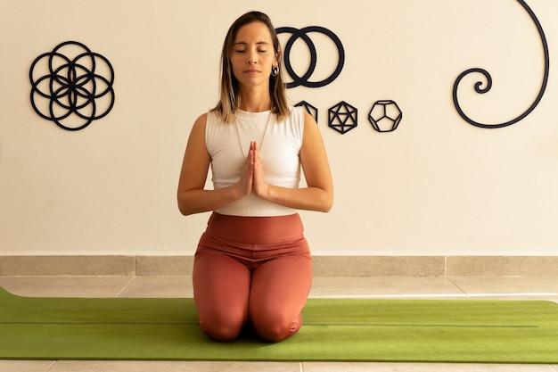 Mulher jovem meditando com as mãos em posição de oração no estúdio de ioga