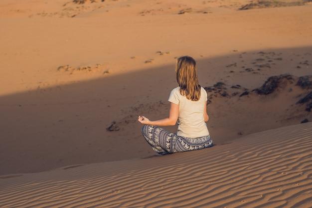 Mulher jovem meditando em um deserto de areia radiante ao pôr do sol ou amanhecer