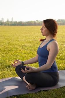 Mulher jovem meditando em um tapete de ioga ao ar livre