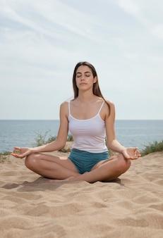 Mulher jovem meditando na areia