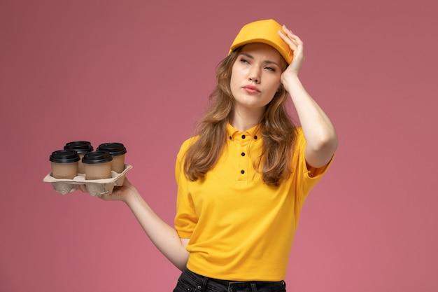 Mulher jovem mensageira de uniforme amarelo segurando copos de plástico de café marrom com expressão estressada na mesa rosa-escuro. serviço de entrega de uniforme.