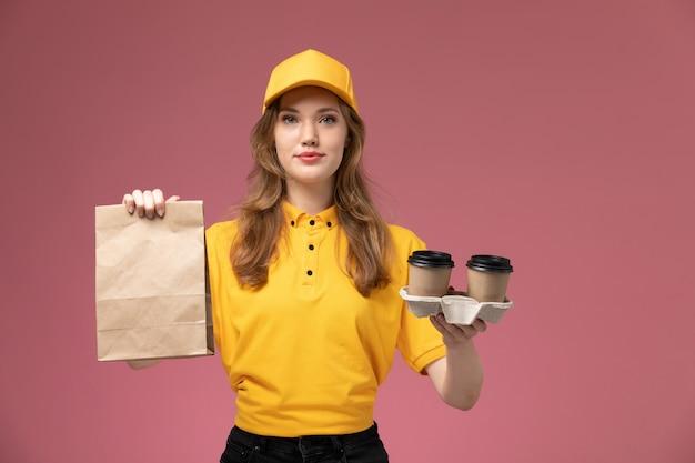 Mulher jovem mensageira de uniforme amarelo segurando copos de plástico de café marrom e um pacote de comida na mesa rosa-escuro. serviço de entrega de uniforme