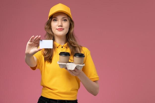 Mulher jovem mensageira de uniforme amarelo segurando copos de plástico de café marrom junto com um cartão branco na mesa rosa-escura.