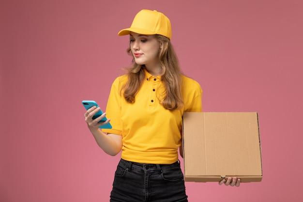 Mulher jovem mensageira de uniforme amarelo segurando o telefone e o pacote de comida na mesa rosa escura. serviço de entrega de uniforme