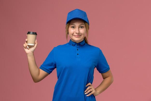 Mulher jovem mensageira de uniforme azul posando de frente e segurando uma xícara de café na parede rosa, entregadora de uniforme de serviço