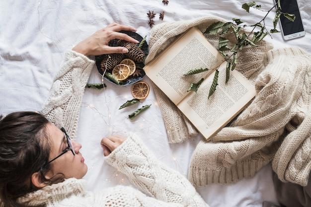 Mulher jovem, mentindo cama, com, livro