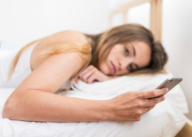 Mulher jovem, mentindo cama, usando, telefone móvel