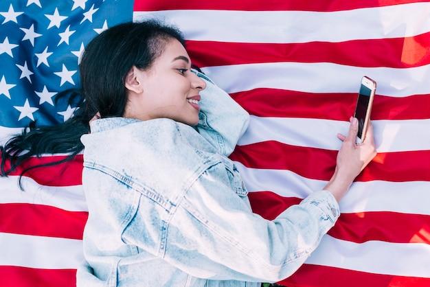 Mulher jovem, mentindo, ligado, bandeira americana, e, usando, smartphone