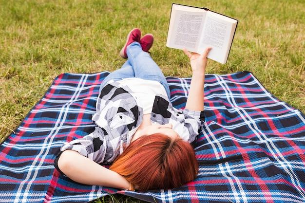 Mulher jovem, mentindo, ligado, cobertor, livro leitura
