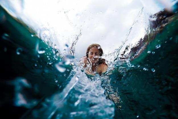 Mulher jovem mergulha na água vista debaixo dos borrifos de água conceito de férias de verão pule para a piscina
