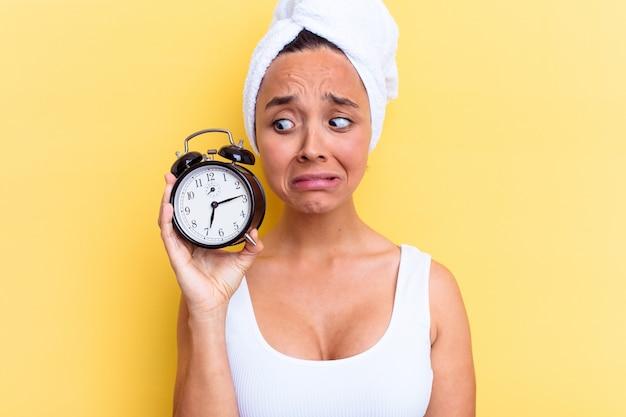 Mulher jovem mestiça atrasada para o trabalho isolada em fundo amarelo