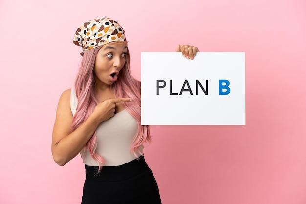 Mulher jovem mestiça com cabelo rosa isolada em um fundo rosa segurando um cartaz com a mensagem plano b com expressão de surpresa