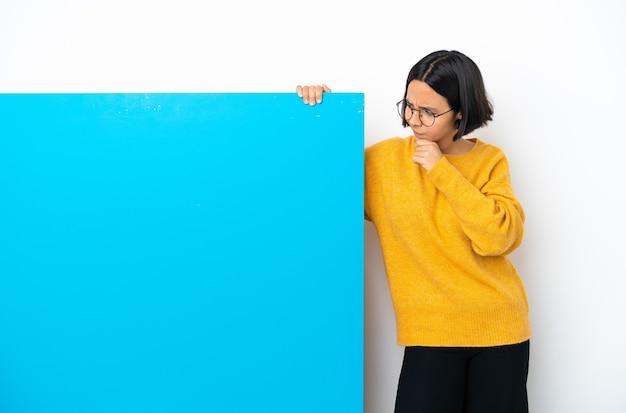 Mulher jovem mestiça com um grande cartaz azul isolada, tendo dúvidas e pensando
