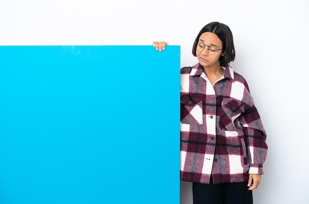 Mulher jovem mestiça com um grande cartaz azul isolada tendo dúvidas enquanto olha para o lado