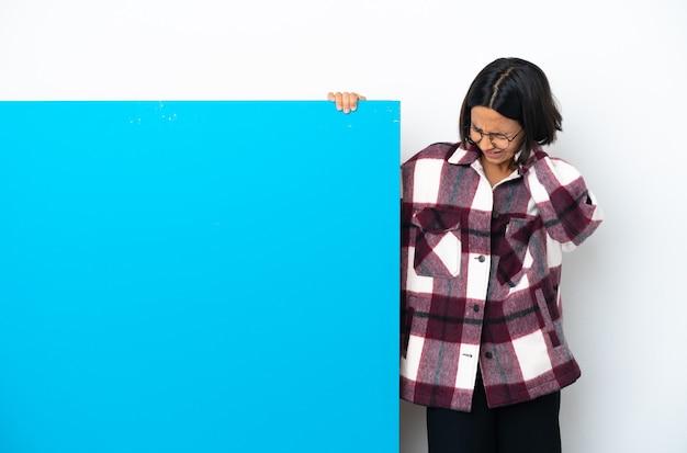 Mulher jovem mestiça com um grande cartaz azul isolado no fundo branco e com dor de pescoço