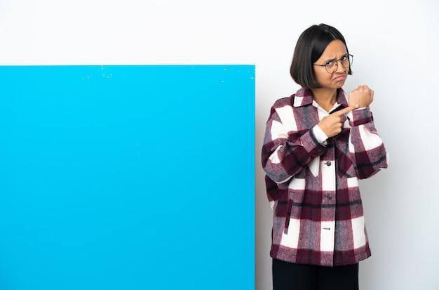 Mulher jovem mestiça com um grande cartaz azul isolado no fundo branco fazendo o gesto de estar atrasado