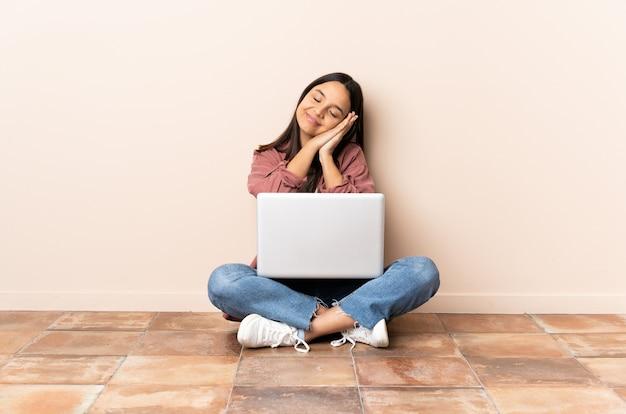 Mulher jovem mestiça com um laptop sentada no chão fazendo gestos para dormir