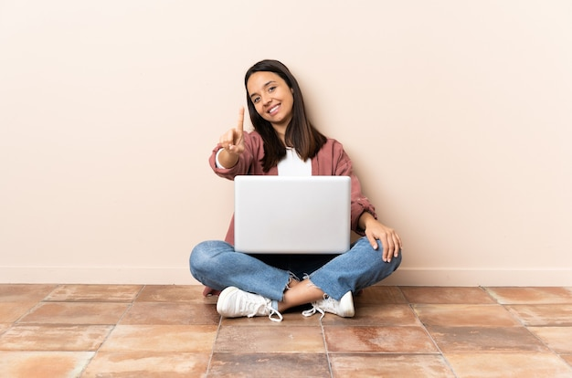 Mulher jovem mestiça com um laptop sentada no chão, mostrando e levantando um dedo