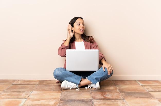 Mulher jovem mestiça com um laptop sentada no chão ouvindo algo colocando a mão na orelha